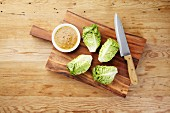 Cos lettuce with a bowl of mustard dressing and a large knife on a wooden board