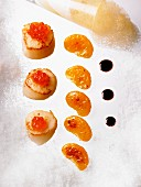 Scallops with salmon caviar, fried mandarin segments and a balsamic vinegar reduction