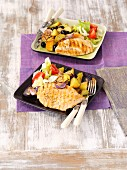 Grilled chicken breast with baked potatoes, garlic and red onions