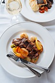Sliced duck breast served on fried potatoes with roasted root vegetables