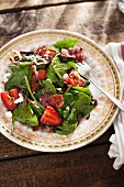 Spinach salad with strawberries, basil, bacon, goat's cheese and balsamic dressing