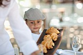 A little boy wearing a cap and holding a tray of fresh croissants