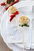 Two Christmas cake pops decorated with white cooking chocolate and nut brittle