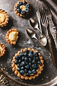 Silver cutlery and various different sized blueberry tartlets with lemon cream, one with a bite taken out