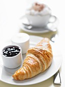 A fresh croissant with blueberry jam and butter
