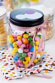 Storage jar of colourful gumballs decorated with pink ribbon