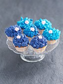 Cupcakes decorated with blue buttercream and sugar flowers