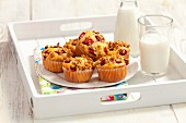 Strawberry muesli muffins and milk on a tray