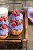 Cupcakes decorated with berry cream and fresh berries on a wooden tray
