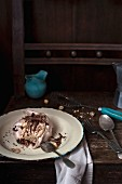 A chocolate meringue with coffee cream, nuts and chocolate shavings