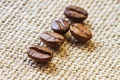 Five coffee beans on a piece of jute