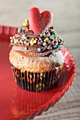 A romantic cupcake decorated with coloured sprinkles and a heart