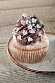 A cupcake decorated with chocolate buttercream and sugar hearts