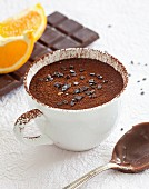 A cup of chocolate-orange pudding dusted with cocoa powder with ingredients in the background