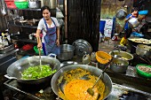 An oriental woman cooking curry and vegetables in large woks (Klong Toey Market, Bangkok, Thailand)