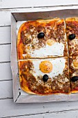 Homemade pizza with tuna, olives and fried egg