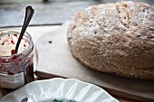 A whole loaf of homemade wholemeal bread and jam on a wooden board