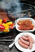 Marinated pork steaks, sausages and vegetables in front of a hot barbecue
