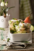 Spicy pear and cucumber salad with peppermint, pine nuts and yogurt sauce