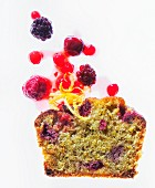 A slice of pistachio cake with berries and lemon zest