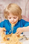 A little boy eating spaghetti with his fingers