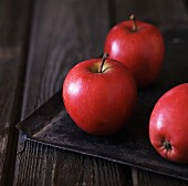 Red apples on a black baking tray