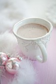 A cup of hot chocolate between feathers and Christmas baubles