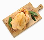 A raw corn-fed chicken on a chopping board