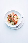 Salmon trout fillet on a bed of Spätzle (Swabian egg noodles) with tomatoes and horseradishes
