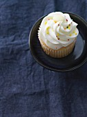 A vanilla cupcake decorated with colourful sprinkles