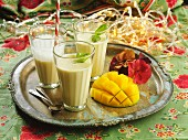 Three glasses of mango lassi on a tray