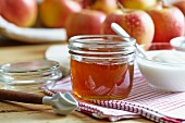 A jar of honey, yogurt and fresh apples