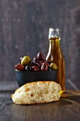 A slice of unleavened bread, olives and a bottle of olive oil