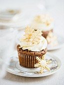 A chocolate cupcake topped with buttercream and Christmas sugar decorations