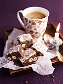 Berliner Brot (German Christmas biscuits) on a piece of white paper with a cup of hot coffee