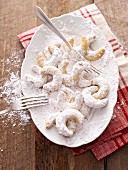 Vanilla crescent biscuits being rolled in icing sugar
