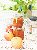 Two jars of apple chutney and fresh apples