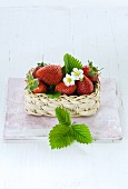 Strawberries with leaves and flowers in a little basket