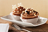 Cupcakes topped with chocolate cream and nuts for Christmas