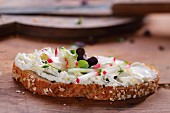 A slice of bread topped with cream cheese, radishes and cress