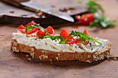 A slice of bread topped with cream cheese, tomatoes and rocket