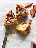 Three slices of gluten free plum cake with almonds and crumbles on parchment paper