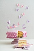 A sponge cake filled with buttercream, topped with pink fondant icing and decorated with fondant flower petals and paper butterflies
