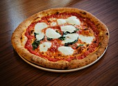 A margherita pizza on a wooden table