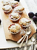 Plum and poppyseed crumble cakes with icing sugar