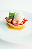 A strawberry tartlet with vanilla ice cream and mint