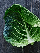 A savoy cabbage leaf on a weathered wooden surface