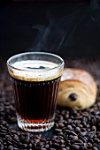 Coffee and a chocolate croissant on coffee beans