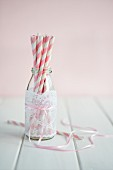 Straws in an empty smoothie bottle decorated with a piece of lace