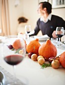 A table laid for Thanksgiving decorated with pumpkins and onions